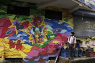 "A Nepalese schoolboy looks at a mural while standing beside a vegetable vendor in Kathmandu on August 20, 2013. Some 60 artists have been involved in the project called ""Kolor Kathmandu"" which began in January and will culminate on Thursday with the launch of a book of photographs on the murals"