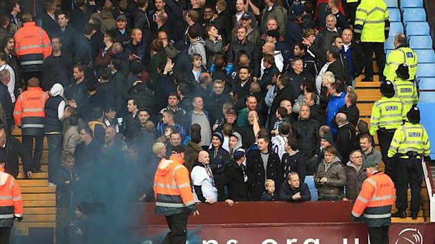 Police and stewards go into the away supporter's stand after a flare is thrown and hits assistant referee David Bryan (not in picture) (PA Photos)