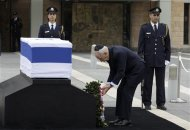 Israel's President Shimon Peres (C) lays a wreath near the flag draped coffin of former Israeli prime minister Ariel Sharon as he lies in state at the Knesset, Israel's parliament, in Jerusalem January 12, 2014. REUTERS/Ronen Zvulun