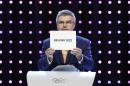 President of the International Olympic Committee (IOC) Thomas Bach opens the envelope announcing that Beijing has won the bid to host the 2022 Winter Olympic Games at the 128th International Olympic Committee session in Kuala Lumpur, Malaysia, Friday, July 31, 2015. Almaty and Beijing competed for the right to host the 2022 Winter Olympic Games. (AP Photo/Joshua Paul)