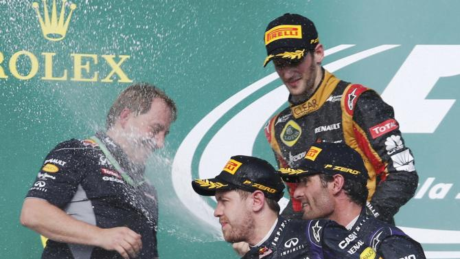 Sebastian Vettel of Germany, Mark Webber of Australia and Romain Grosjean of France spray champagne next to Matt Cadieux during celebrations on the podium after the Austin F1 Grand Prix at the Circuit of the Americas in Austin