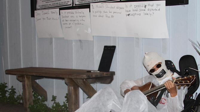 Alternative folk singer Michelle Shocked sits outside Moe's Alley nightclub in Santa Cruz Calif., and strums her guitar on Thursday, March 28, 2013. After her show was canceled when she made an anti-gay slur earlier this month. Shocked had her face covered and her mouth taped shut. She dressed in a white disposable safety suit and invited people to write on it. (AP Photo