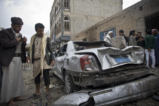 People look at a car destroyed by Saudi-led airstrikes in Sanaa, Yemen, Wednesday, May 27, 2015. In a new report Wednesday, World Health Organization Chief Margaret Chan said that Yemen's conflict