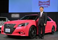 Akio Toyoda, president of Japanese auto giant Toyota, poses with the company's flagship Crown sedan in Tokyo on December 25, 2012. He will get behind the wheel in the Nurburgring 24-hour endurance race in Germany later this month, a company spokesman said Wednesday