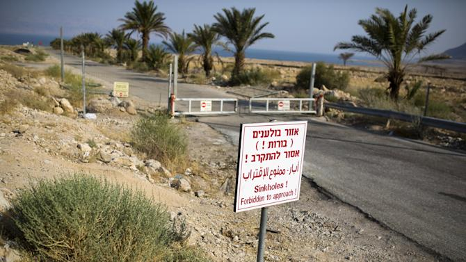 A sign warning of sinkholes is seen at the entrance to an abandoned tourist resort on the shore of the Dead Sea