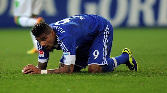 Schalke's Kevin-Prince Boateng kneels on the  pitch  during the Bundesliga soccer match between Borussia Moenchengladbach and FC Schalke 04 at Borussia Park in Moenchengladbach, Germany, Saturday Dec. 7, 2013