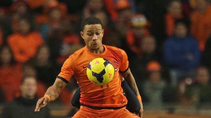 Netherlands' Memphis Depay, foreground, and Colombia's Santiago Arias, rear, vie for the ball during the international friendly soccer match between Netherlands and Colombia at ArenA stadium in Amsterdam, Netherlands, Tuesday Nov. 19, 2013. The match ended in a draw