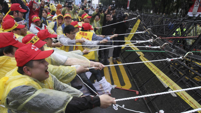 Taiwanese workers try to pull a road block down during a protest on May Day in Taipei, Taiwan, Wednesday, May 1, 2013.  More than 10,000 Taiwanese workers took to the streets in Taipei Wednesday to protest a government reform plan that will cut pension payouts to ease Taiwan's worsening fiscal problems. The protesters said the payout cuts reflect a longstanding government policy to bolster economic growth at the expense of workers' benefits  and compromised workplace safety.  (AP Photo/Chiang Ying-ying)