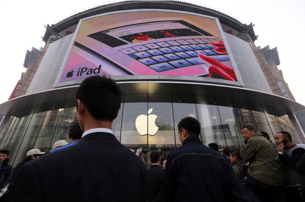 Security staff watch over a crowd gathered for the opening of a new Apple store in Beijing's Wangfujing shopping district