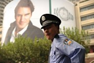 "A security guard stands under a giant poster of top-ranked men's tennis player Roger Federer in Shanghai. The organisers have tightened security around Federer, who has arrived in Shanghai with his family, after he was targeted by an unknown blogger who said he planned to ""assassinate"" the player, in a bizarre posting on a popular Chinese website"