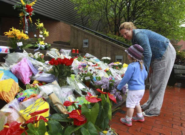 Caroline (R) and Lily Connors leave flowers on the steps of the RCMP headquarters in Moncton, N.B. (Reuters)