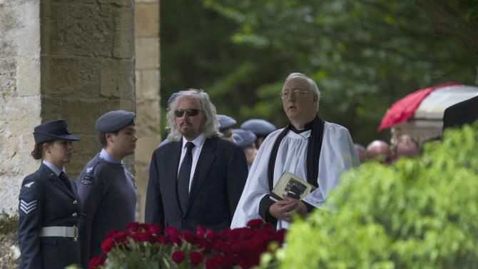 Barry Gibb, third left, walks with the vicar to the graveside following the funeral of his brother Robin Gibb's outside St Mary's Church in Thame, England, Friday, June 8, 2012. Robin Gibb a member of the iconic Bee Gees pop group died May 20, after a long battle with cancer. (AP Photo/Alastair Grant)