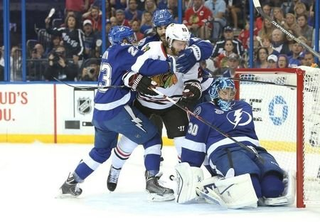 Jun 6, 2015; Tampa, FL, USA; Chicago Blackhawks left wing Brandon Saad (20) is grabbed by Tampa Bay Lightning right wing J.T. Brown (23) and center Brian Boyle (11) after a collision with goalie Ben Bishop (30) in the first period in game two of the 2015 Stanley Cup Final at Amalie Arena. Kim Klement-USA TODAY Sports