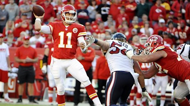Kansas City Chiefs quarterback Alex Smith (11) throws a pass under pressure from Houston Texans inside linebacker Brian Cushing (56) in the first half at Arrowhead Stadium.