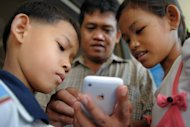 "File illustration photo shows a man look at his mobile phone with his children in Phnom Penh. Children must be taught to reflect before hitting the ""send"" button on something they might later regret, refrain from anonymous comments, and not to believe everything they read or see online"