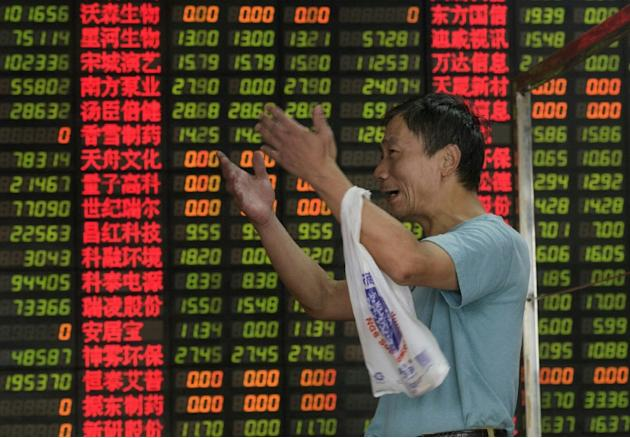 An investor reacts in front of screens showing stock market movement at a brokerage house in Shanghai on September 1, 2015