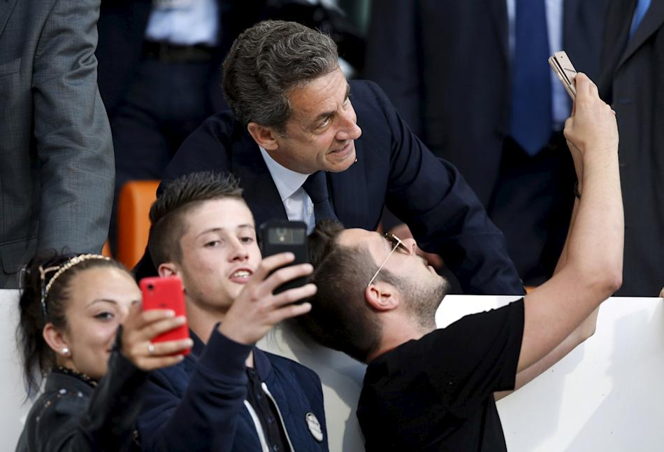 Former French President Nicolas Sarkozy takes a selfie with supporters during the French Ligue 1 soccer match between Montpellier and Paris St Germain at the Mosson Stadium in Montpellier