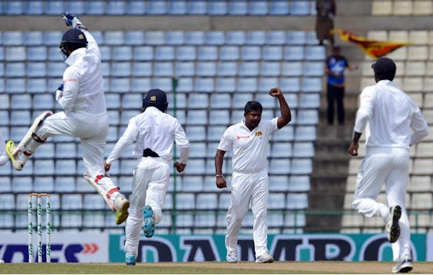 Sri Lanka's Rangana Herath (2nd R) celebrates with his teammates after the dismissal of Australia's captain Steven Smith during the second day of their opening Test match between Sri Lanka and