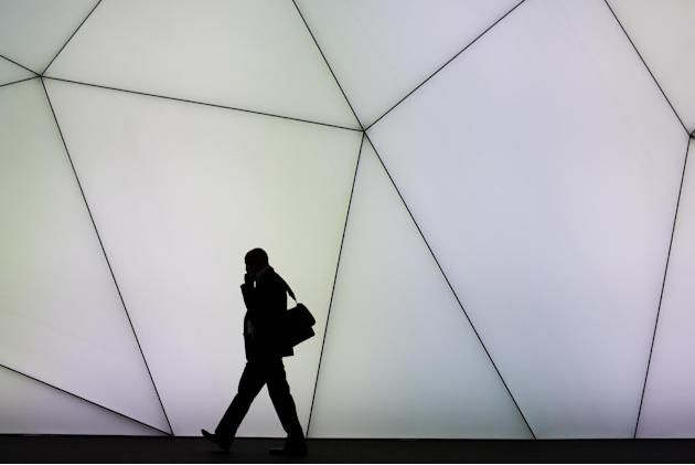 A visitor uses his phone inside a pavilion at the Mobile World Congress, the world's largest mobile phone trade show, in Barcelona, Spain, Tuesday, March 3, 2015. (AP Photo/Emilio Morenatti)