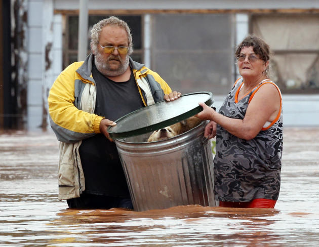 George and Susan Kruger make one of three trips with their animals from their flooded house to safety on Sunday, May 24, 2015 in Purcell, Okla. Rising water from overnight rains began to rise early in