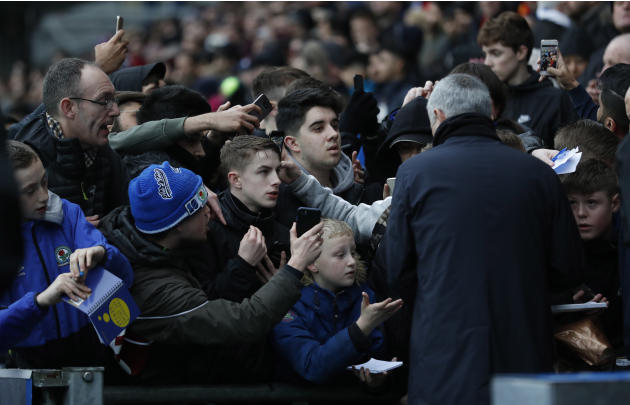 Manchester United manager Jose Mourinho signs his autograph for fans