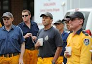 Australian opposition leader Tony Abbott (C) listens to a bushfire briefing as he prepares to help in his capacity as a member of the fire service, in New South Wales, on January 9, 2013. Fires have been raging across Australia for nearly a week and while many have been contained, 126 are still burning and at least 15 remain out of control