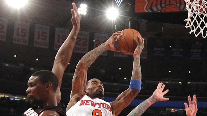 New York Knicks' J.R. Smith (8) goes to the basket against Miami Heat's Chris Bosh (1) and Chris Andersen (11) during the second half of an NBA basketball game Saturday, Feb. 1, 2014, in New York.  Miami won 106-91