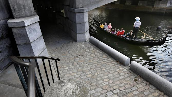 A gondola and its passengers glide along the Woonasquatucket River as it passes under a bridge in downtown Providence, R.I., Tuesday, July 16, 2013. Temperatures in Rhode Island climbed into the 90s in many places Tuesday. (AP Photo/Steven Senne)