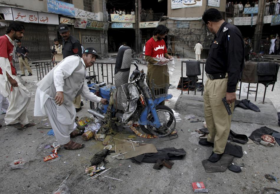 Security officials and rescue workers check the site of a bomb blast in Quetta