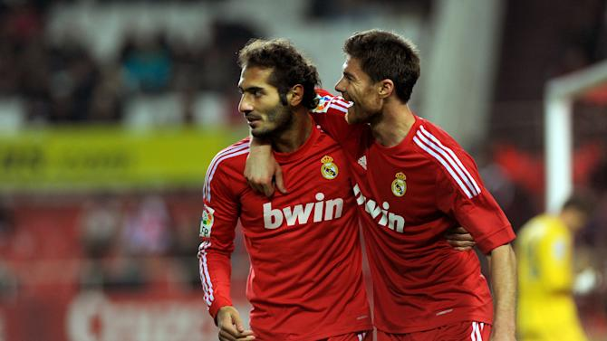 Real Madrid's midfielder Turkish Hamit Altintop (L) celebrates with midfielder Xabi Alonso (R) after scoring during their Spanish league football match Sevilla FC vs Real Madrid on December 17, 2011 at Ramon Sanchez Pizjuan stadium in Sevilla.    AFP PHOTO/ JORGE GUERRERO (Photo credit should read Jorge Guerrero/AFP/Getty Images)