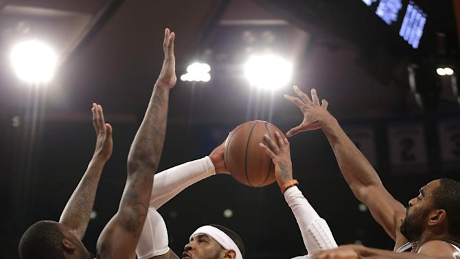 New York Knicks' Carmelo Anthony, center, is fouled by Brooklyn Nets' Andray Blatche, left, while driving to the basket past Blatche and Alan Anderson during the first half of the NBA basketball game at Madison Square Garden, Monday, Jan. 20, 2014, in New York