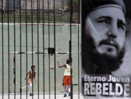 Children play soccer behind a picture of Cuba's former president Fidel Castro in Havana