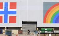 A man cycles past a banner of the Norwegian flag and a rainbow hanging on a warehouse in Oslo in this June 20, 2012 file photo. REUTERS/Cathal McNaughton/Files