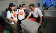 Association of South East Asian Nations (ASEAN) election observers check a polling station in Yangon on April 1, 2012. In an attempt by the government burnish its reform credentials, foreign observers and journalists have been invited to witness the vote