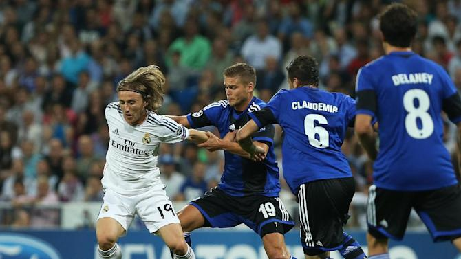 Real Madrid's Luka Modric from Croatia, left, duels for the ball with FC Copenhagen's Rurik Gislason, second left, during the Champions League group B soccer match between Real Madrid and FC Copenhagen at the Santiago Bernabeu stadium in Madrid, Spain, Wednesday, Oct. 2, 2013
