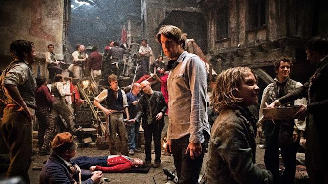 """This undated publicity photo provided by Universal Pictures shows Oscar®-winning director, Tom Hooper, center, and Daniel Huttlestone, right, as Gavroche on the set of Hooper's new film, """"Les Misérables,"""" the motion-picture adaptation of the beloved global stage musical adapted from Victor Hugo's novel. (AP Photo/Universal Pictures/James Fisher)"""