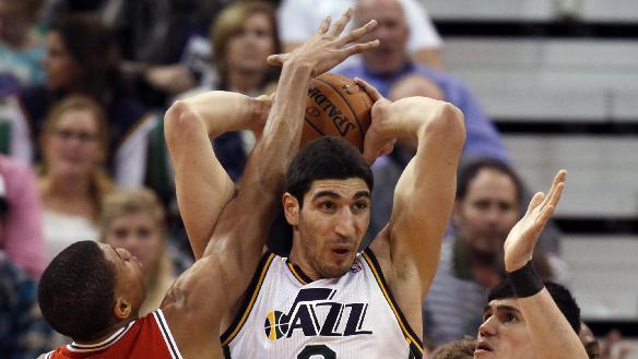 Utah Jazz's Enes Kanter (0) looks to pass as Milwaukee Bucks' Giannis Antetokounmpo (34) and Milwaukee Bucks' Ersan Ilyasova (7) put on pressure in the first half of an NBA basketball game Thursday, Jan. 2, 2014, in Salt Lake City