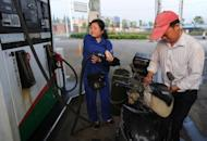 A motorcyclist fills up at a petrol station in Hefei, east China's Anhui province in May 2012. China said that it would slash fuel prices for the third time since May, after growth in the world's second largest economy slowed and softened demand