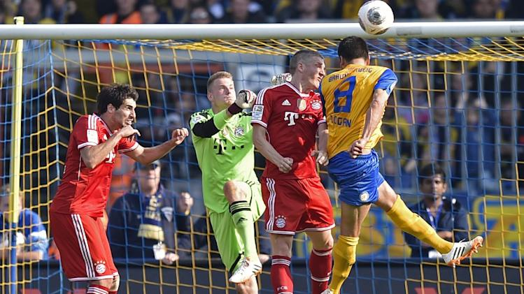 Braunschweig's Deniz Dogan of Turkey, right, misses to score against Bayern's Bastian Schweinsteiger, goalkeeper Lukas Raeder and Bayern's Javier Martinez of Spain, from right, during the German Bundesliga soccer match between Eintracht Braunschweig and Bayern Munich in Braunschweig, Germany, Saturday, April 19, 2014