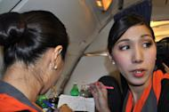 Transsexual fight attendant Phuntakarn Sringern (R) works onboard a Thai PC Air flight between Bangkok and Hong Kong. Fledgling Thailand-based carrier PC Air has hired four transgender cabin crew in a highly publicised recruitment drive that has divided opinion over whether the move is in the spirit of equality or exploitation