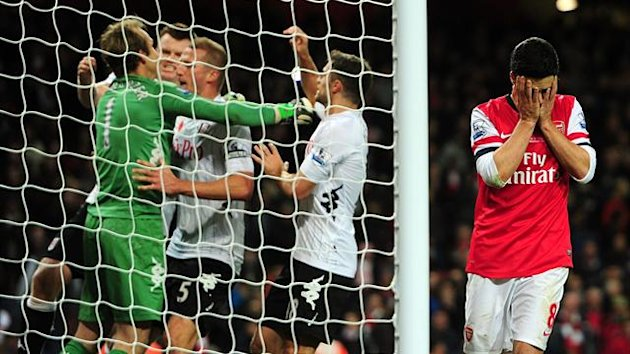 Arsenal's Mikel Arteta (right) holds his head in his hands after having a last-minute penalty saved by Fulham goalkeeper Mark Schwarzer (left) who celebrates with team-mates