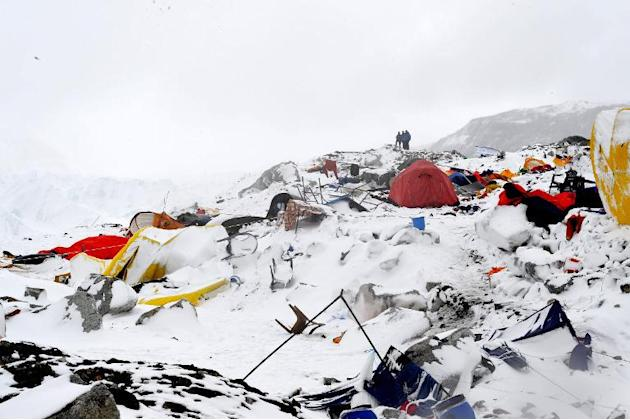 People look at the devastation after an avalanche triggered by an earthquake flattened parts of Everest Base Camp