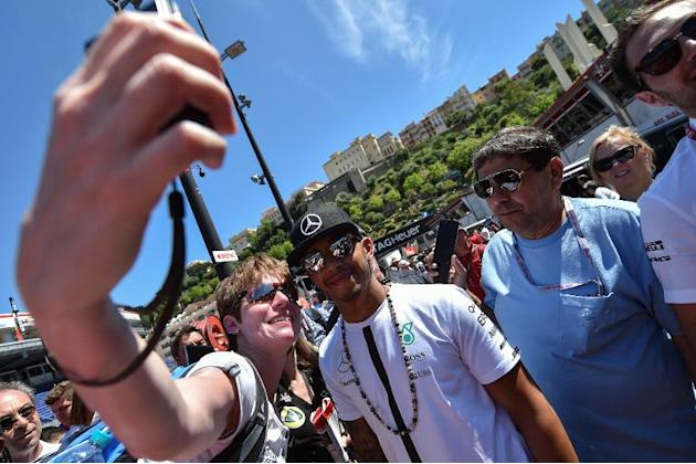 Mercedes AMG Petronas F1 Team's British driver Lewis Hamilton (C) poses for a picture with a supporter ahead of the Monaco Formula One Grand Prix in Monte Carlo on May 22, 2015