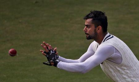 India's captain Kohli prepares to catch the ball during a practice session ahead of their fourth and final test cricket match against South Africa in New Delhi