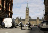 Armed RCMP officers race across a street on Parliament Hilll following a shooting incident in Ottawa October 22, 2014. REUTERS/Chris Wattie