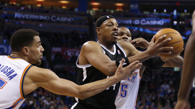 Brooklyn Nets forward Paul Pierce, center, drives between Oklahoma City Thunder guard Thabo Sefolosha , left, and forward Kevin Durant in the first quarter of an NBA basketball game in Oklahoma City, Thursday, Jan. 2, 2014. (AP Photo/Sue Ogrocki)