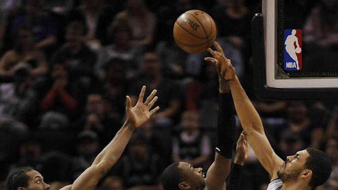 San Antonio Spurs power forward Jeff Ayres, right, blocks Toronto Raptors guard Terrence Ross (31) during the first half of an NBA basketball game on Monday, Dec. 23, 2013, in San Antonio