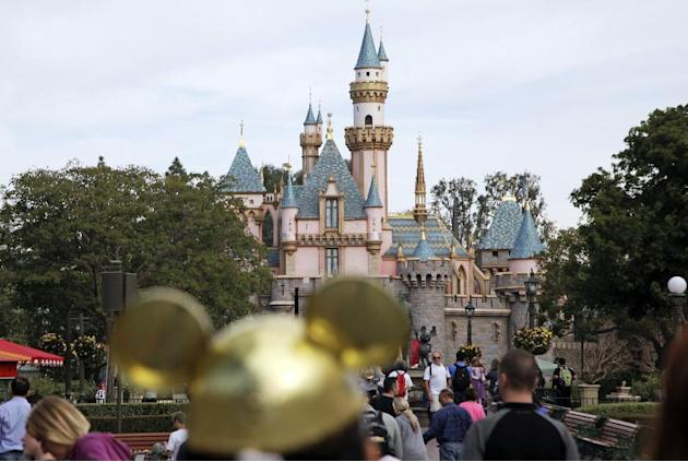 FILE - In this Jan. 22, 2015 file photo, visitors walk toward the Sleeping Beauty's Castle in the background at Disneyland Resprt in Anaheim, Calif. California health officials have declared an en
