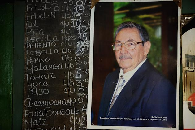HAVANA, CUBA - JANUARY 24: A photograph of Cuban President Raul Castro hangs next to a chalk board listing the prices of fruit and vegetables in an open air market in the Jesus Maria neighborhood of Habana Vieja January 24, 2015 in Havana, Cuba. After the Cuban government expanded the list of accepted private small businesses between 2010 and 2012, about 1 million people, 20 percent of the Cuban workforce, can now be classified as wholly in the private sector. Diplomats from the United States and Cuba held historic talks this week that could restore diplomatic ties and mark the end of more than 50 years of of Cold War-era hostility between the two countries. (Photo by Chip Somodevilla/Getty Images)