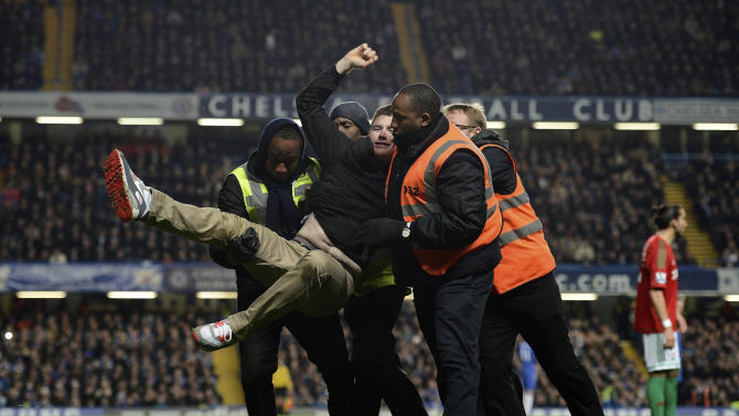 A football fan is carried off the pitch during English League Cup semi-final soccer match in London